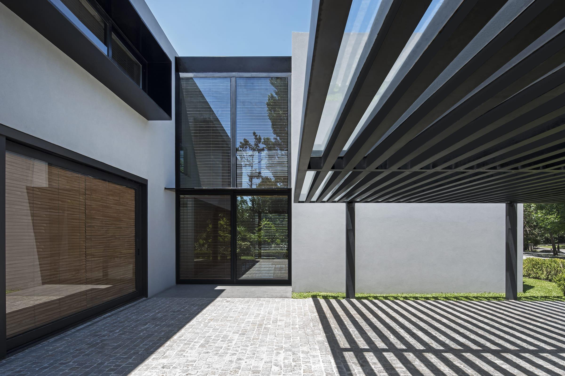 El acceso es un espacio-fuelle que se manifiesta con una estructura metálica y vidrio.