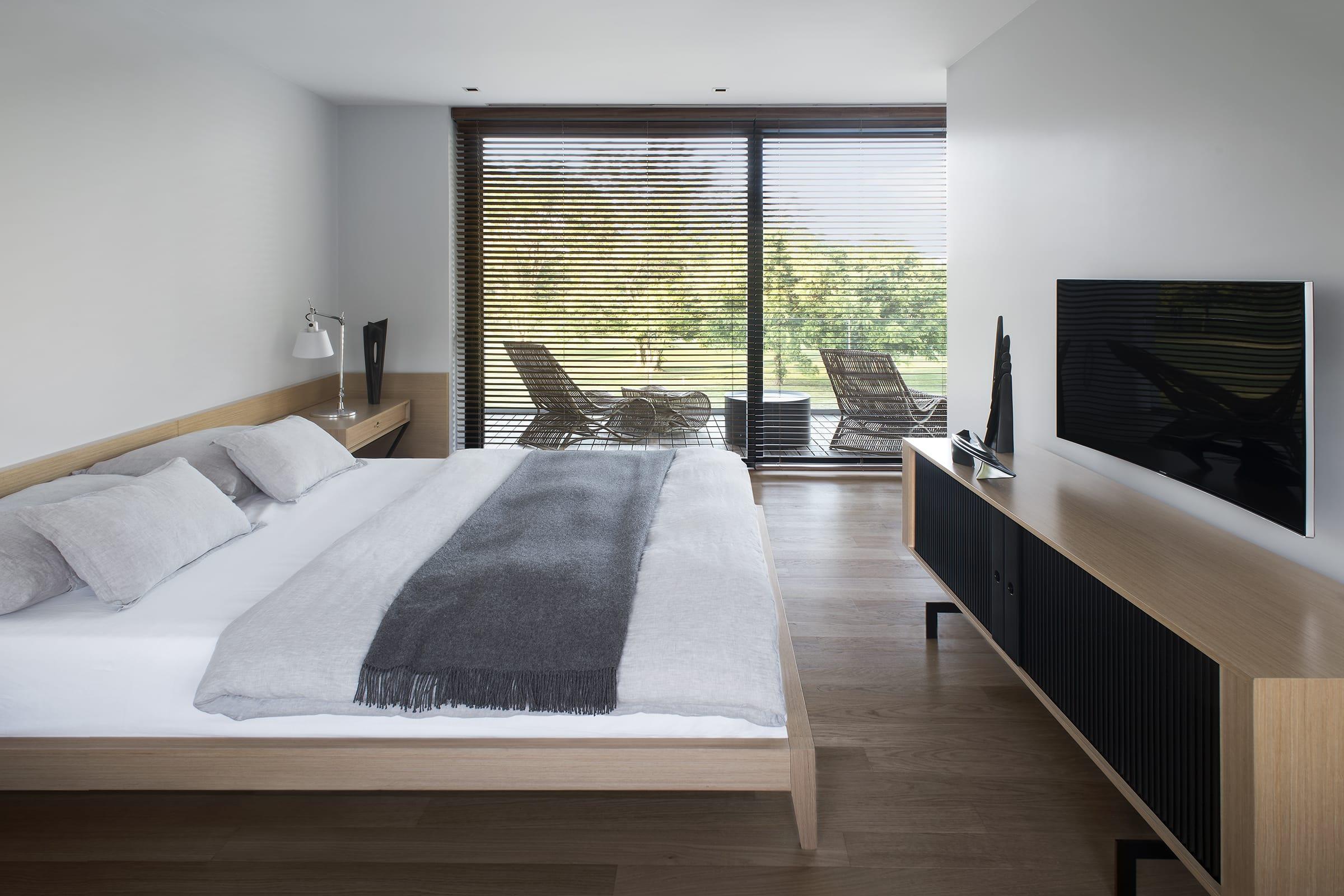 El dormitorio principal se expande hacia un balcón con baranda de vidrio.
