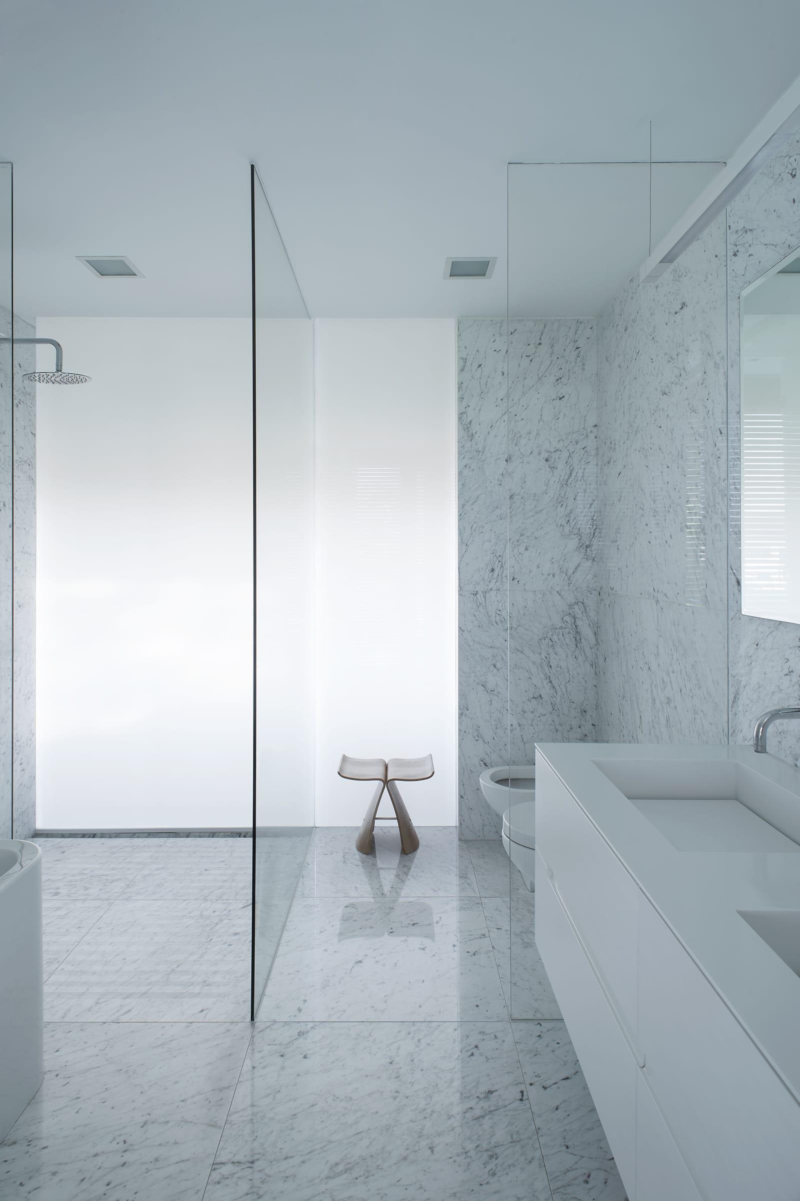 Una pared de vidrio blanco lleva luz natural difusa al interior de los baños.