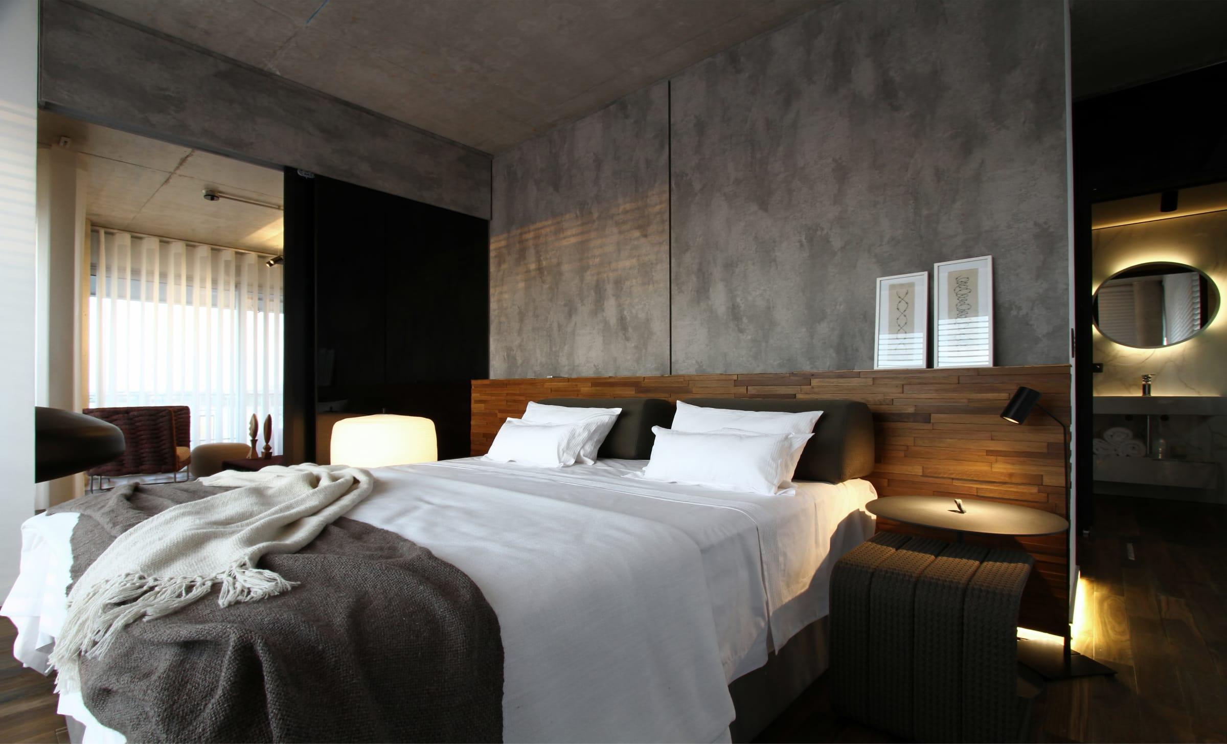 El respaldo de la cama está resuelto con revestimiento Panel 3D Roble (Patagonia Flooring). El piso multiestrato de Palo Santo (Patagonia Flooring) integra el dormitorio y el antebaño, sutilmente iluminado con tiras led línea Lumiere (Atrim).