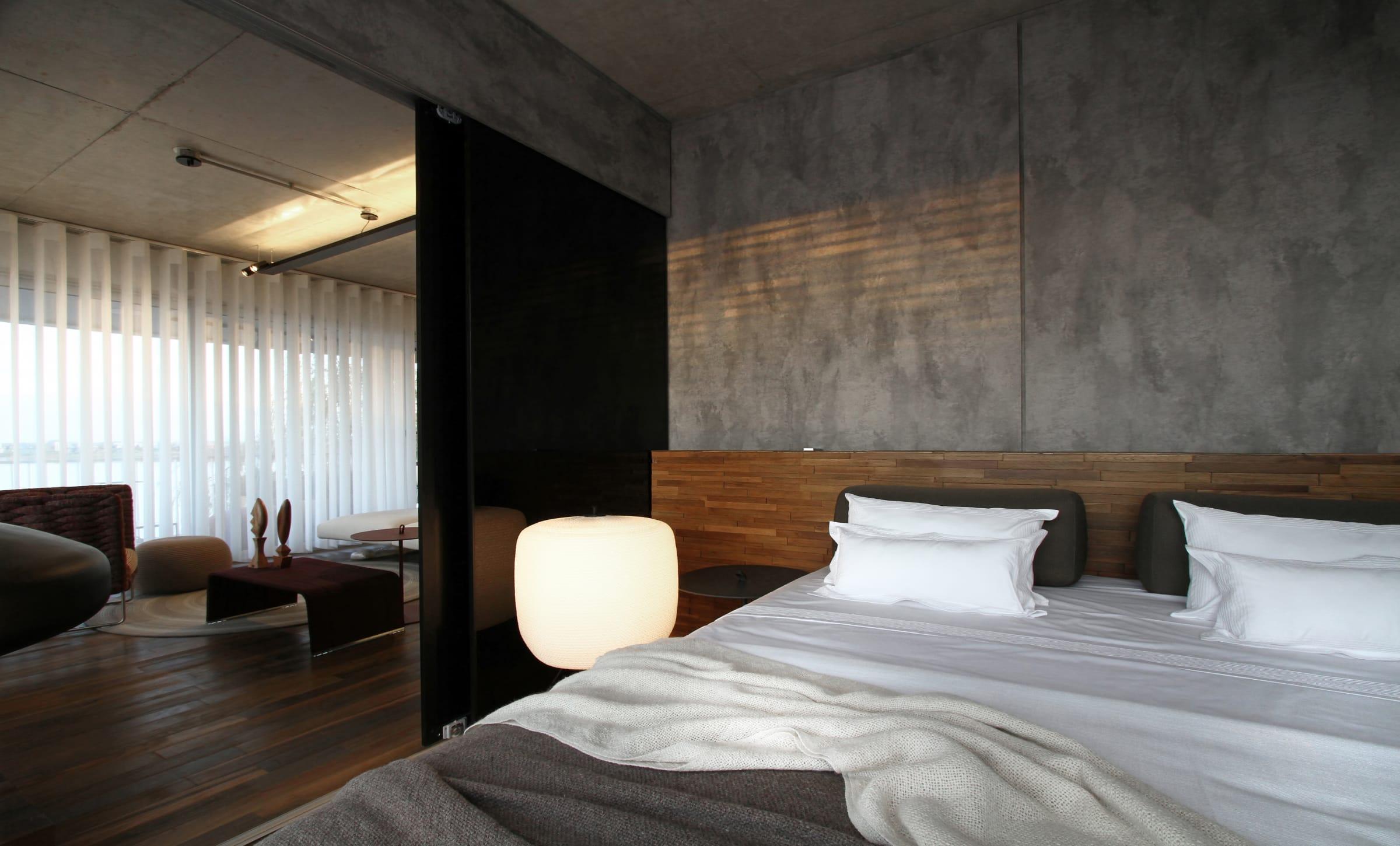 Paneles de vidrio negro integran el dormitorio con el living. Piso de palo Santo (Patagonia Flooring) y paredes revestidas con panel modelo Street, simil cemento (Faplac).