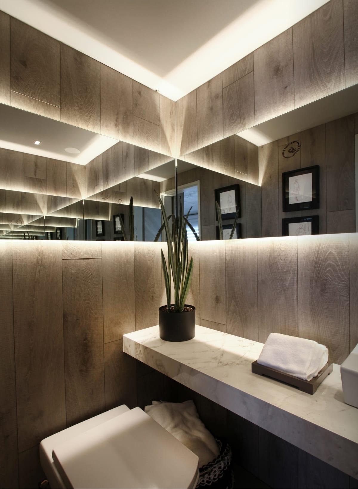 Los espejos en esquina e iluminación para crear un efecto escenográfico en el toilette.